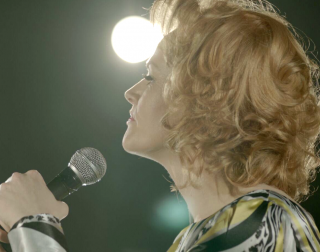 Side profile of a blonde woman, defiantly clutching a microphone
