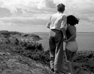 Black and white. A man and a woman look out over the ocean from a cliff.