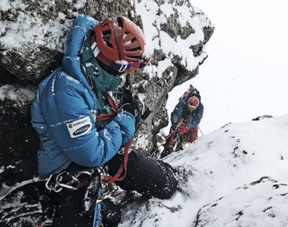 Two people in helmets and harnesses climb a snowy mountain