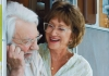 A retired couple wearing glasses sit in the doorway of their Winnebago, laughing.