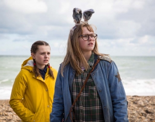 Two young girls standing on a pebbled beach looking inland, one wears rabbit ears, the other a yellow coat