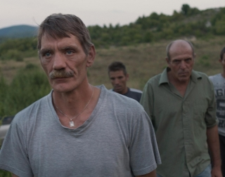 Group of men looking grim faced, walking in the countryside