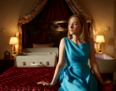 A young woman in a blue dress sits on a bed looking out a window