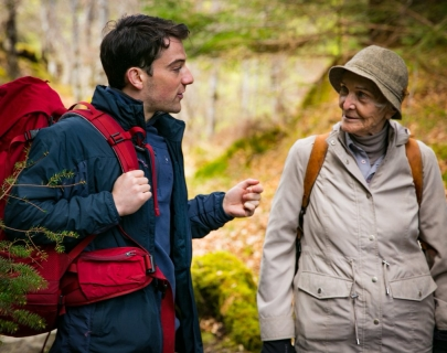 An old woman in outdoor gear looking at a young man with a red rucksack who is talking to her
