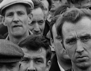Black and white. A crowd of dock workers stand together.
