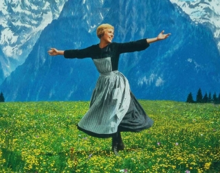 A young woman spinning in a green meadow surrounded by alpine peaks