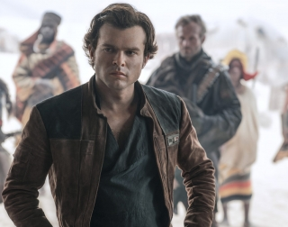 A young Han Solo in a brown leather jacket walks towards the camera