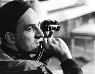 Black and white. Director Ingmar Bergman sits in a chair, holding a camera.