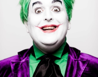 Comedian Justin Moorhouse dressed as the joker with green hair, white paint on his face, red lipstiick and a purple suit