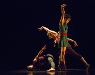 Three dancers perform on a black background and floor, dressed in bright colours