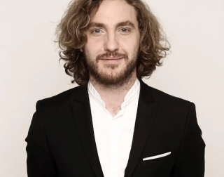 Comedian Seann Walsh wearing a black suit and standing against a neutral background