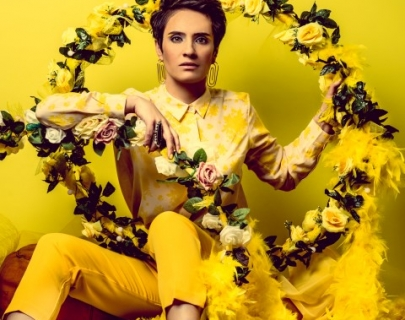 Comedian Jen Brister wearing yellow shirt, trousers and boots, surrounded by yellow roses against a yellow background