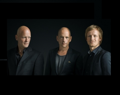 Three men wearing dark suits standing against a black background