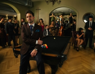 Pianist Scott Bradlee sitting on a pool table surrounded by other performers in vintage clothes