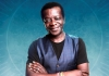 Comedian Stephen K Amos smiling with his arms crossed against a light blue background