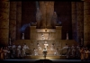 A dark set reproducing Egyptian statues and pyramids with a big ensemble in white robes