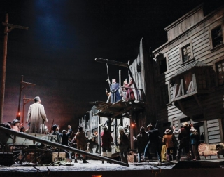 A dark western setting with a crowd looking up to a gallows platform