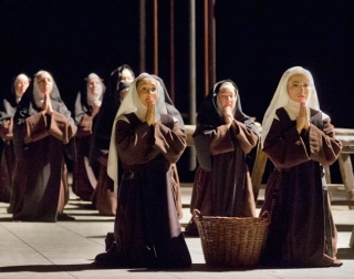 Several women dressed as nuns kneeling in prayer