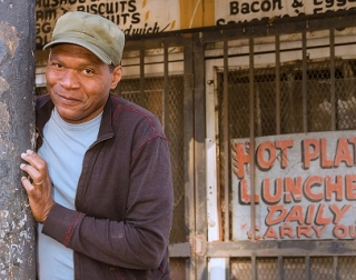 Musician Robert Cray leans against a post, wearing a green cap and a blue t shirt, outside a closed diner.