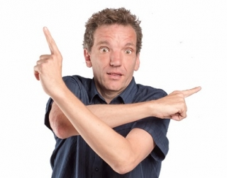 Henning Wehn stands against a white back ground with his arms crossed, pointing in different directions.