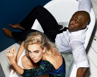 A woman in a sparkly dress and a man in a suit lying in a white bath tub