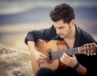 Miloš Karadaglić sits on a rock, playing a guitar.
