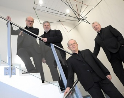 Four musicians from the Coull Quartet stand on a glass and chrome staircase, wearing black suits