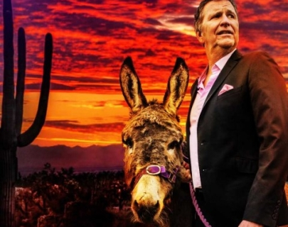 Comedian Stewart Francis in a brown suit standing next to a donkey with a desert sunset in the background