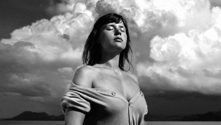 Black and white. A woman stands against a sunny sky with her eyes closed.