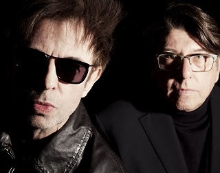 Two men in black clothes, wearing glasses, pose against a black background