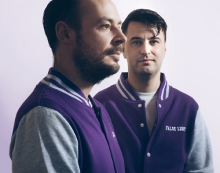 Two men in purple and grey football jackets against a neutral background