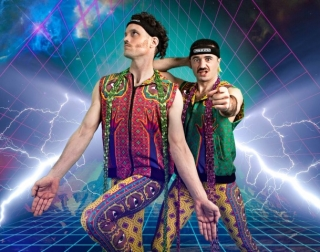Two men in colourful clothes against a digitally designed background with lighting and geometrical neon shapes