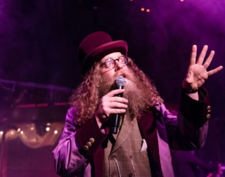 A man with glasses, long brown hair and beard holding a microphone, dressed in purple clothes and a top hat