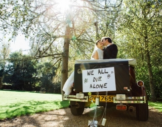 "A newly married couple kissing in a convertible black car with the sign ""We All Die Alone"" in an outdoor setting"