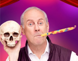A grey-haired man with a party horn in his mouth and a skull in his hand