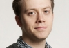 Image of Owen Jones wearing a checked shirt and a dark jumper against a neutral background
