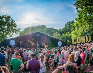 A fish-eye view of a festival stage, with a audience in front of it, on a summer's day. A sign on the right says, 'Lunar'.