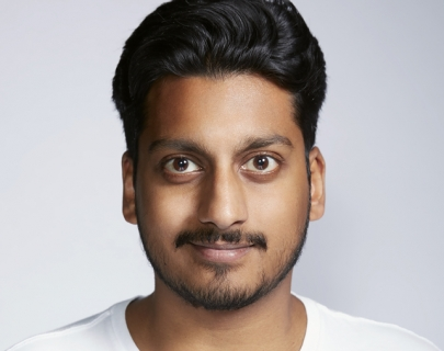 An image of comedian Ahir Shah wearing a white t-shirt against a neutral background