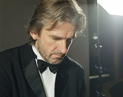 Pianist Barry Douglas sits at a piano, wearing a black suit and a black bow tie.