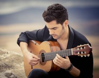 Miloš Karadaglić sits on a rock, playing guitar.