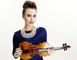 Violinist Jennifer Pike holds her violin, wearing a blue dress and beaded necklace.