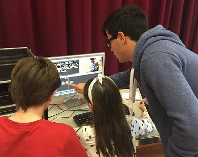 Two children work on editing a video, directed by a workshop leader.