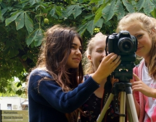 Three girls filming using a camera on a tripod