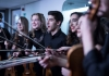 A group of young musicians dressed in black holding violins