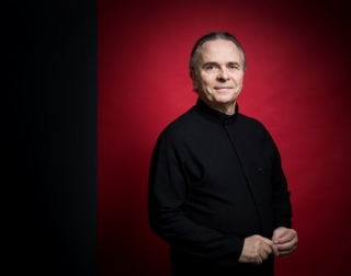 Conductor Sir Mark Elder in a black outfit against a red background