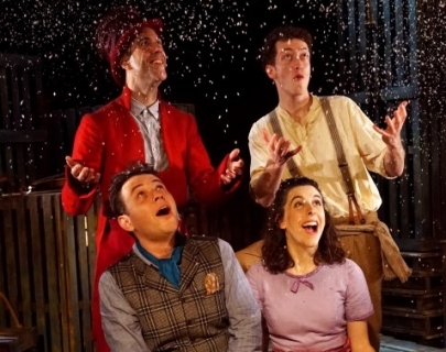 Four actors on stage looking up at fake snow falling down