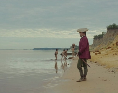 A man wearing a red officer's jackets and hat stands on a beach looking out to sea
