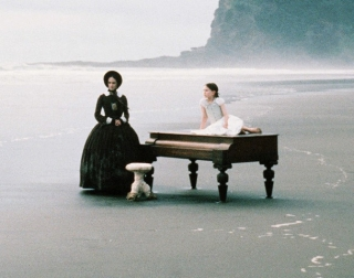 A woman in a black dress and hat stands on a beach next to a piano with a child in a white dress sitting on it