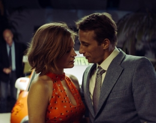 A man in a suit and a woman in an orange halter-neck dress stare into each other's eyes