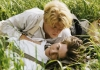 Two young men wearing white shirts and braces lie affectionately together in some long grass